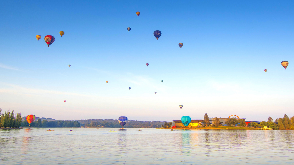 Dozens of hot air balloons rising up high in the Canberra sky